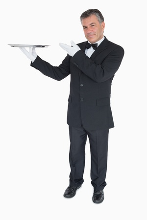 Happy waiter presenting an empty silver tray photo