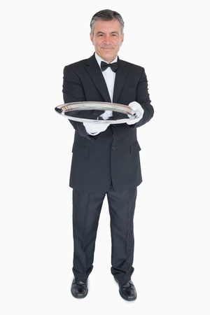 Smiling waiter holding out empty silver tray photo