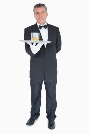 Man in suit holding silver tray with glasses of whiskey photo