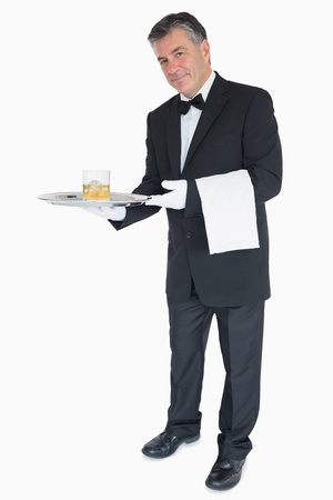 Smiling waiter offering whiskey with ice on tray photo