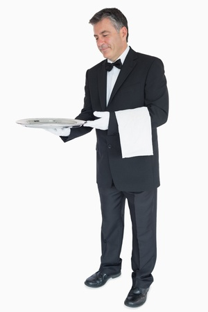 Waiter in suit offering something on silver tray with towel over his arm photo