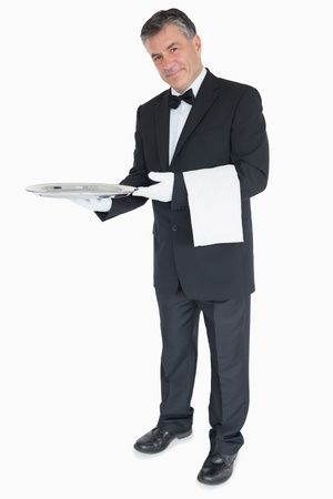 Smiling waiter standing against the white background holding silver tray with towel over his arm photo