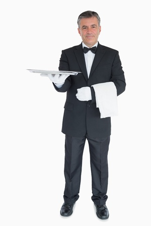 Smiling waiter holding out silver tray with towel over his arm photo