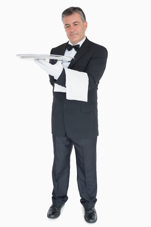 Smiling waiter looking at silver tray he is holding photo