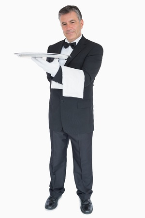 Happy waiter with silver tray and towel over his arm photo