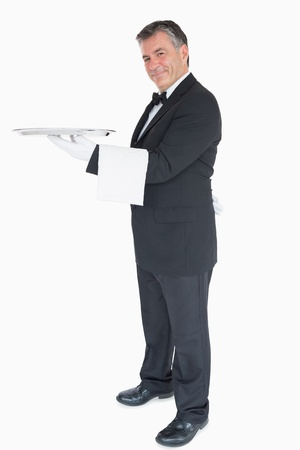 Smiling waiter holding silver tray while is looking into the camera photo