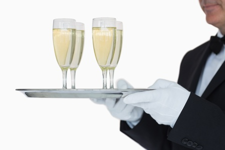 Waiter carrying silver tray full glasses of champagne  photo