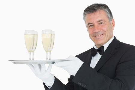 Smiling waiter holding silver tray with glasses full of champagne photo