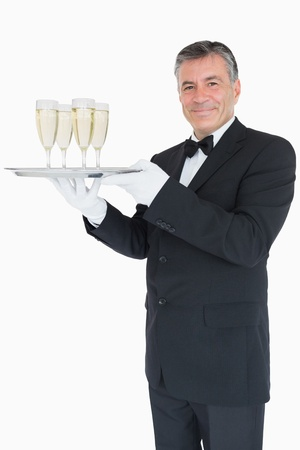 Smiling waiter holding silver tray with champagne glasses on white background photo