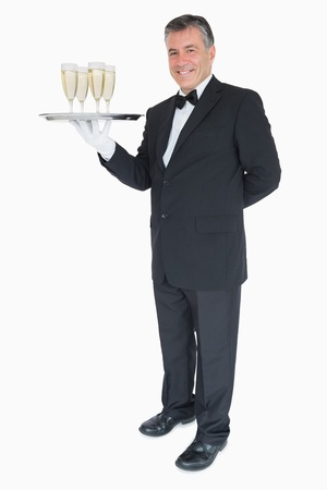 Smiling waiter standing with silver tray of champagne photo