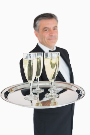 Smiling waiter holding out tray with champagne flutes photo