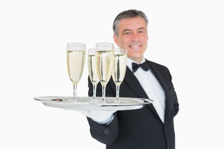 Smiling waiter serving silver tray full of champagne glasses  photo