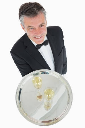 Waiter standing with silver tray of champagne flutes photo