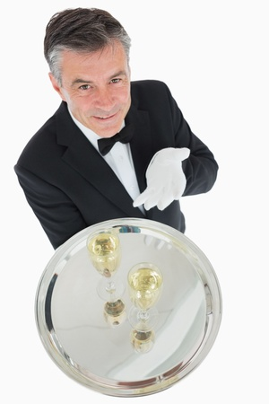 Smiling waiter offering tray with glasses of champagne photo