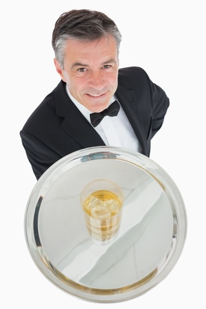 Waiter serving glass of whiskey on a silver tray photo