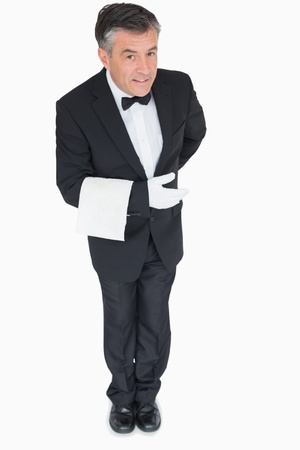 bowing: Smiling waiter bowing down with towel on his arm Stock Photo
