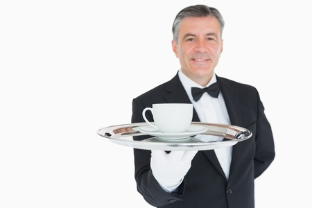 Smiling waiter holding siilver tray with coffee cup  photo