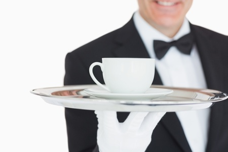 Waiter serving coffee on silver tray photo