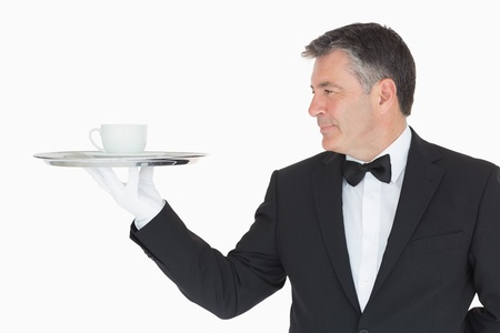 Waiter in suit holding silver tray with cup on white background photo