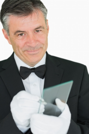 noting: Happy waiter writing on virtual screen on white background Stock Photo