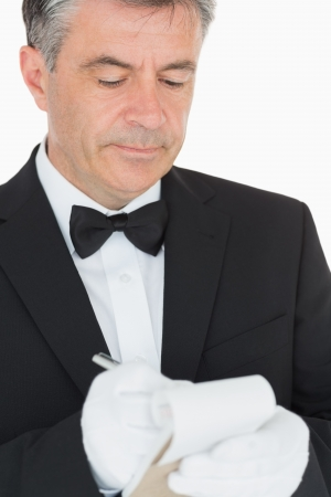 Waiter in suit writing into his notebook photo