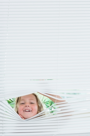 blind child: Smiling girl peeking out of white blinds