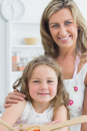 Smiling mother hugging daughter while looking directly into the camera and making salad photo