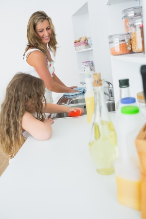 Smiling mother and daughter washing up together Stock Photo - 16075595