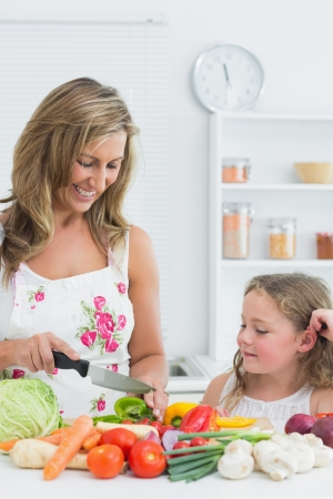 Smiling mother preparing vegetable on the table in the kitchen while her daughter looking on it photo