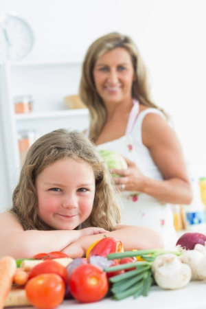 Close up of daughter leaning on table full of vegetables Stock Photo - 16075894