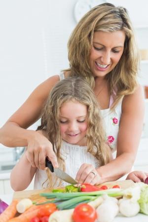 niÑos hablando: Sonriendo madre enseña a su hija cortar varios vehículos