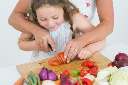Mother helping her smiling daughter to cut tomato photo