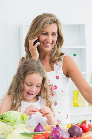 Smiling mother phoning by mobile phone while her daughter working with vegetable photo