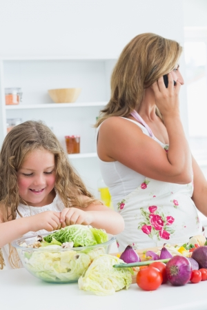 Smiling daughter preparing vegetable salad while her mother phoning by mobile phone photo