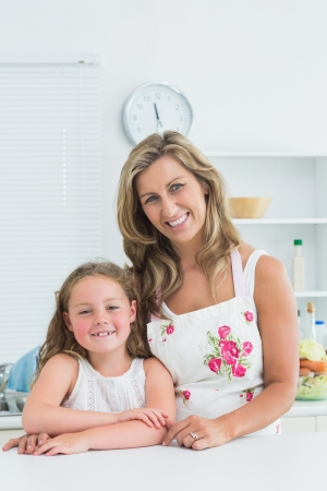 Smiling mother and daughter leaning on table Stock Photo - 16076117