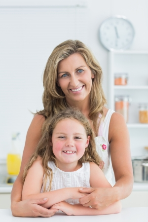 Mother hugging daughter in the kitchen while they look into the camera Stock Photo - 16076002