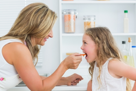 Smiling mother feeding daughter carrot in kitchen Stock Photo - 16076290