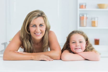 Smiling mother and daughter leaning on white table in the kitchen Stock Photo - 16075487