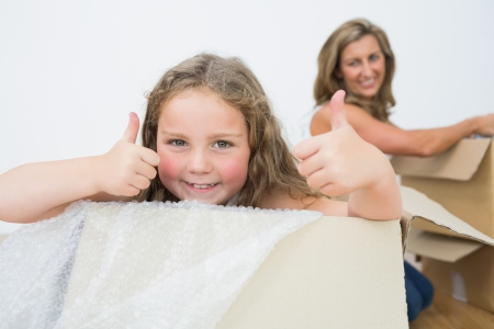 Smiling daughter in box showing thumbs up while her mother unpacking photo