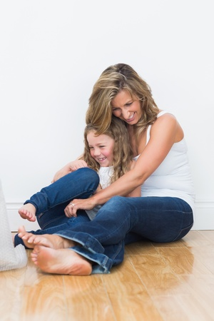 tickling: Laughing mother tickling her daughter on the floor