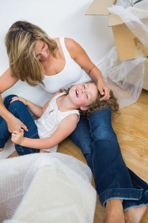 Laughing mother and daughter sitting on the floor and resting photo