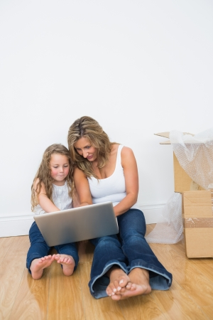 Mother and daughter sitting on floor looking at laptop smiling and pointing photo