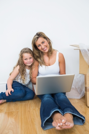 Smiling mother and daughter using laptop while sitting on floor photo