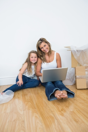 Smiling daughter and mother sitting on the floor and using laptop photo