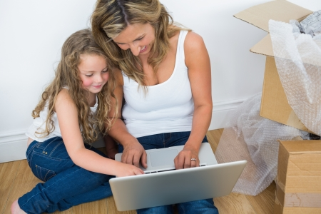 Smiling mother and daughter using laptop while sitting on the floor photo