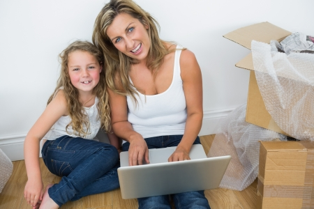 Smiling mother and daughter sitting on the floor and using laptop photo