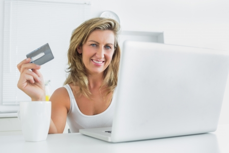 Smiling woman using laptop for online shopping photo