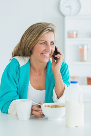 Smiling woman calling during her breakfast photo