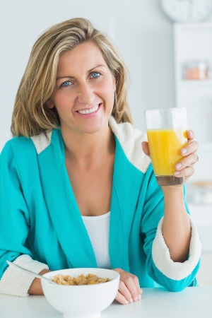Smiling woman holding glass of orange juice photo