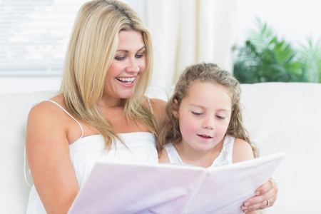 Smiling daughter and mother reading book on the sofa Stock Photo - 16076009